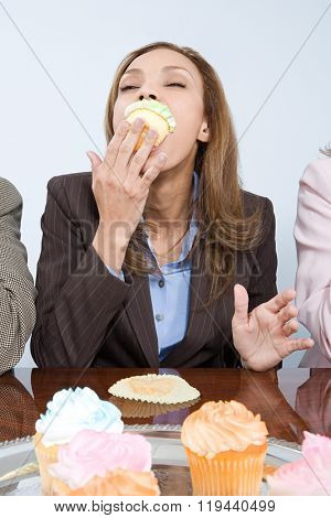 Businesswoman eating cupcake