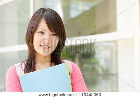 Young Asian adult student standing outside campus building, holding file folder and smiling.