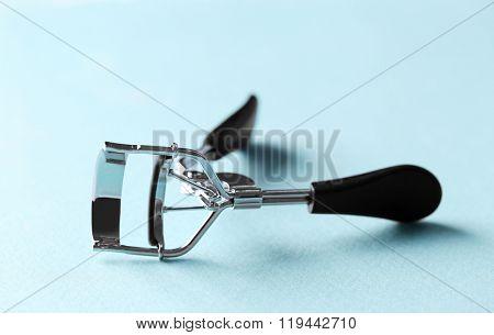 Eyelash curler with black handles on a blue background, close up