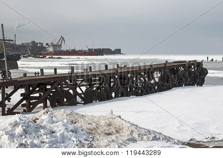 frozen pier at winter yachts