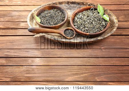 Dry tea in two bowls with green leaves on wooden table background