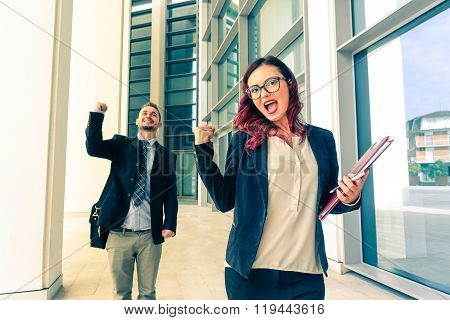 Young Couple Winners In Business With Hands Up And Positive Facial Expression - People Gesture -