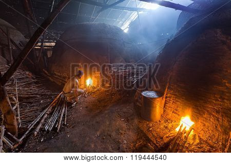 A Charcoal Worker At Work On A Pile Of Slow Burning Wood Charcoal Factory