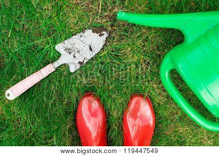 Gardening tools, red garden shoes, secateurs, watering can on the grass, close up. Spring in the garden concept background. Bird eyes view.
