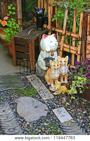 A group of Japanese ceramic cats (called maneki-neko) as lucky charm to decorate the zen styled garden in Japan.