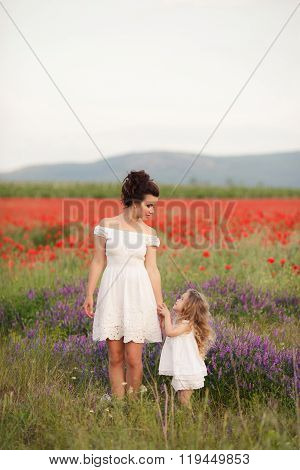 Happy mother and daughter in a field of blooming poppies