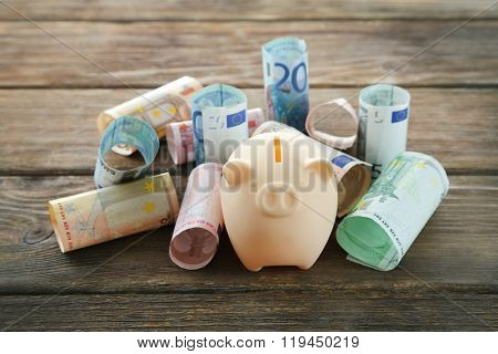 Piggy bank with rolled euro banknotes on wooden background