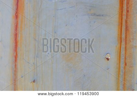 Vertical Streaks Of Rust And Bullet Hole On Sheet Metal