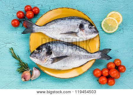 Fresh Dorado Fish On Yellow Plate And Vegetables On Blue Background. Top View.
