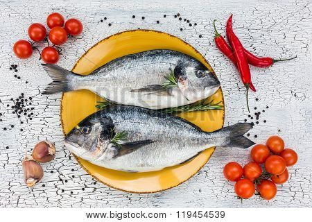 Raw Fresh Dorado Fish On Yellow Plate And Vegetables On White Table. Top View.