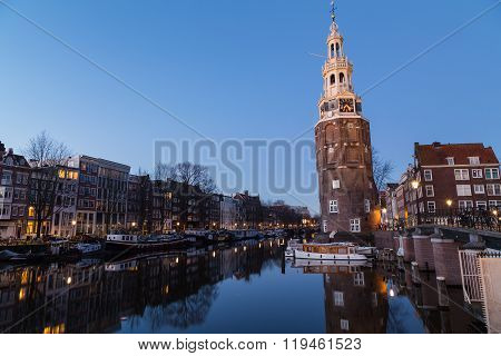 A view along the Oudeschans Canal towards the Montelbaanstoren Tower in Amsterdam at twilight. Building boats and reflections can be seen. There is space for text. ** Note: Soft Focus at 100%, best at smaller sizes