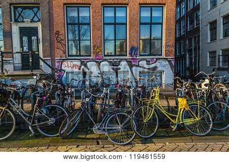 AMSTERDAM NETHERLANDS - 16TH FEBRUARY 2016: Large amounts of bikes chained to fences outside houses in Amsterdam during the day.
