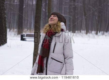 Young beautiful girl close up in winter park enjoys snow fell