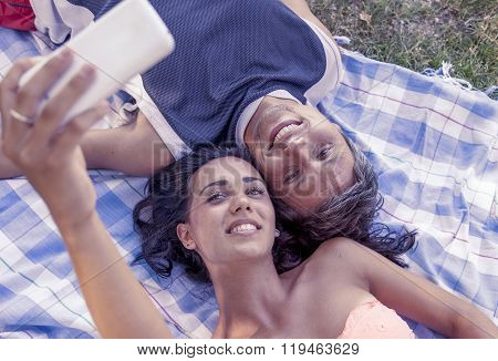 Young Couple Lying On Cloth Take A Selfie Lying In The Park