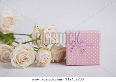 Pink Spotted Gift Box And Creamy Roses On White Background