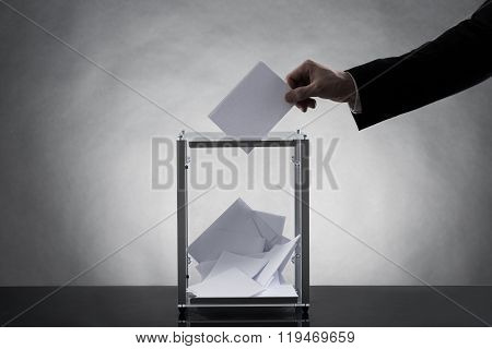 Hand Putting Ballot In Glass Box