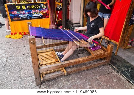 Huangshan Tunxi City, China - Circa September 2015: Girl Weaves Textile Using Traditional Loom  Devi