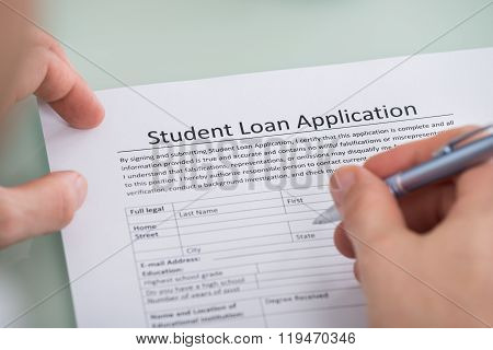 Person Hand Over Student Loan Application Form