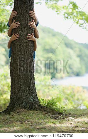 Three people behind tree