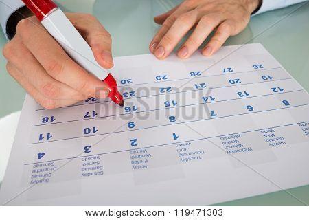 Businessman Highlighting Date On Calendar