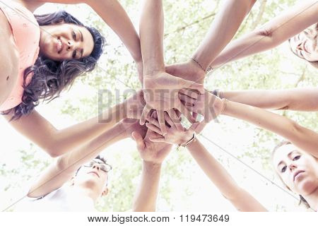Group Of Young Adult Putting Their Hands Together In Circle