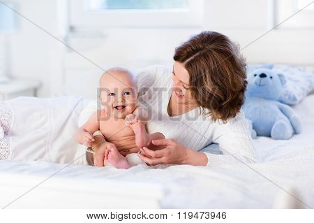 Mother And Baby On A White Bed