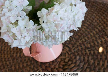 White Plastic Flowers In Pink Flower Vase On The Rattan Weave Table