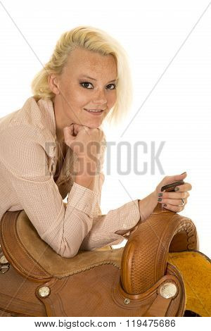 a cowgirl leaning on her saddle with her chin on her fist.