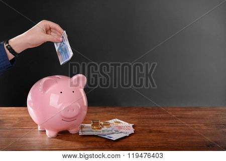 Woman putting euro banknote in pig moneybox