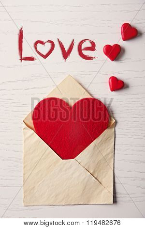 Blank open envelope with hearts on wooden background
