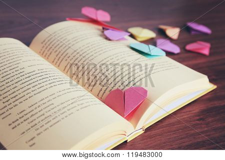 Heart bookmarks for book on wooden table closeup
