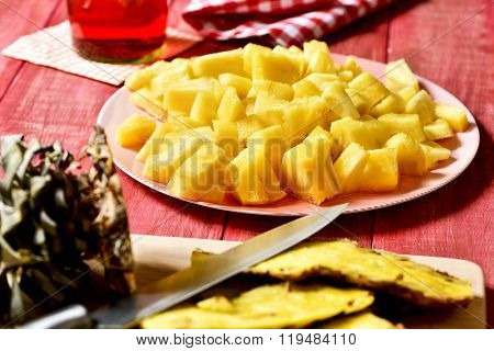 closeup of a plate with freshly diced pineapple on a red rustic wooden table