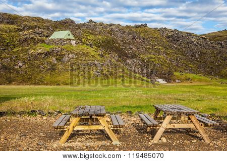 Summer trip to Iceland. The green lawn in the Valley National Park Landmannalaugar. Wooden picnic tables