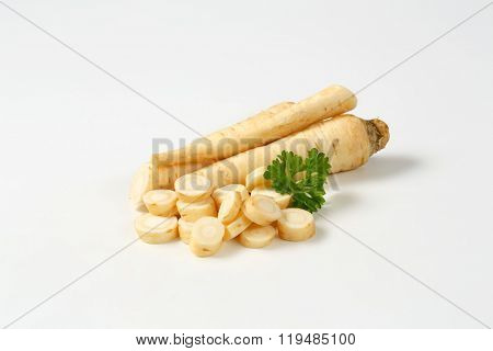 sliced root parsley with leaves on white background