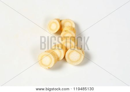 slices of root parsley on white background
