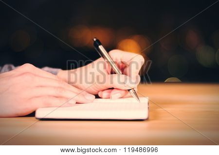 Girl Makes Notes In The Diary On Wooden Table, Close Up