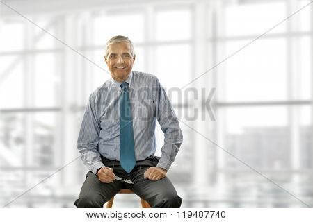Portrait of smiling senior businessman sitting on a stool against office window background while looking at camera.