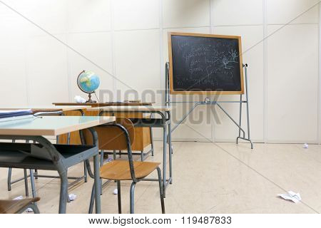 Desks And Blackboard In Classroom At School