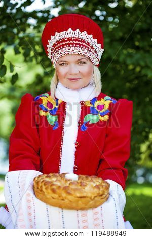 Young woman is dressed in the Russian national dress. She holds in his hands the fresh loaf. It is a custom to meet the guests.