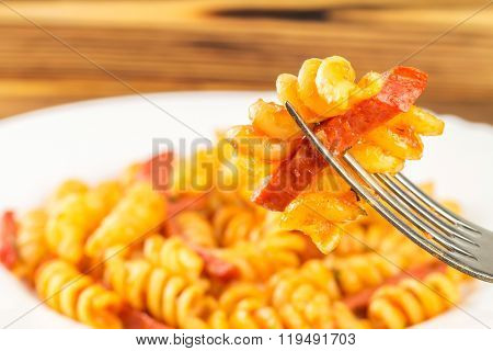 Italian Pasta Fusilli With Tomato Sauce And Sausage Skewered On Fork In Plate, Close-up, Selective F