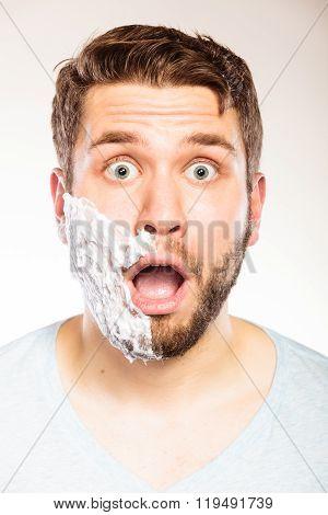Shocked Man With Shaving Cream Foam On Half Face.