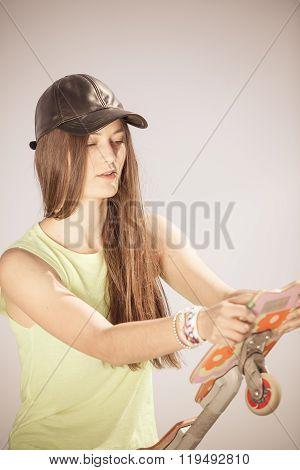 Teen Girl Skater With Skateboard On Street.