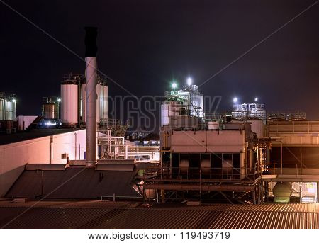 Modern Factory Industrial Plant At Night, Stainless Steel Cooling Tower And Pipelines