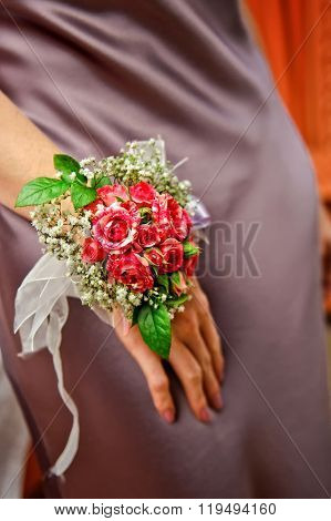 bridesmaid in luxury wedding dress carries to delicate boutonniere with roses