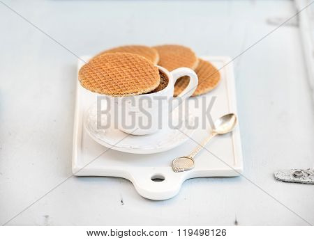 Dutch caramel stroopwafels and cup of black coffee on white ceramic serving board over light blue wo