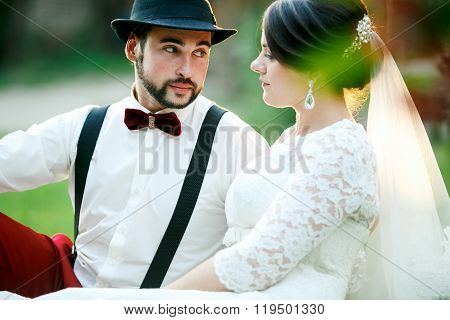 Stylish bride and groom sit on grass in rays of setting sunlight. Newlyweds couple.
