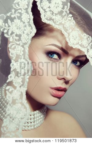 Vintage style portrait of young beautiful bride with stylish make-up and bridal veil