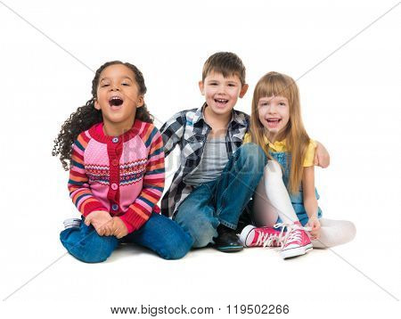 thre cheerful kids sitting on the floor in a studio isolated on white background