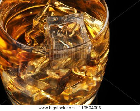 Glass Of Whiskey And Ice On A Black Background