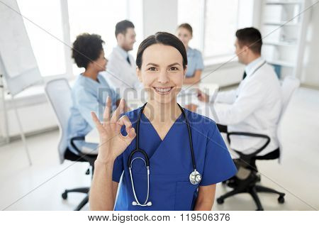 health care, gesture, profession, people and medicine concept - happy female doctor over group of medics meeting at hospital showing ok hand sign